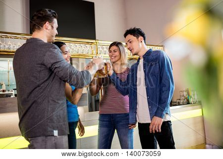 Cheerful young male and female friends toasting wine at bar