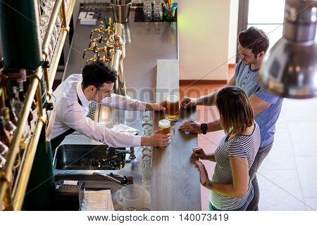 High angle view of bartender serving beer to couple in bar