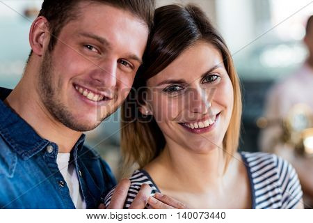 Close-up portrait of smiling young couple at restaurant