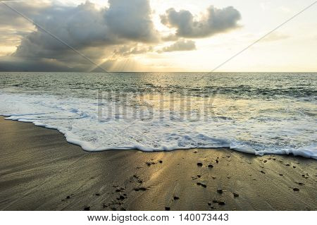 Ocean sunset sun rays is a bright uplifting seascape with sun beams breaking through the clouds as a gentle wave rolls to shore.
