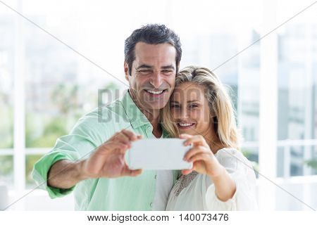 Smiling mid adult couple taking selfie against window at home