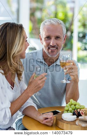 Portrait of mature man holding wineglass while sitting by woman in restaurant