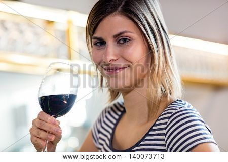 Portrait of beautiful young woman drinking wine in restaurant
