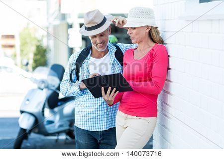 Mature couple looking in notepad while leaning on wall at street