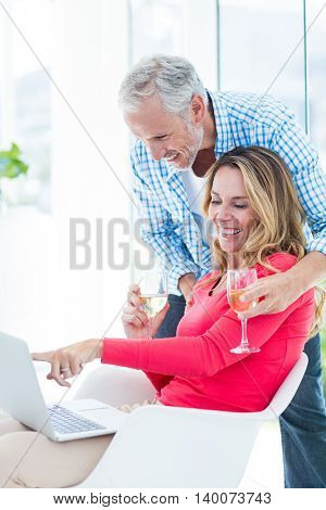 Happy woman pointing at laptop while having wine with husband at home