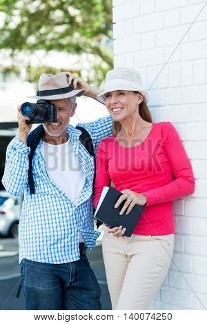 Mature man photographing while standing by wife aganist wall