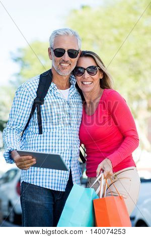Portrait of happy mature couple holding digital tablet and shopping bags against tree
