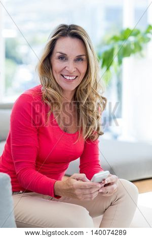 Portrait of happy woman using cellphone on couch at home