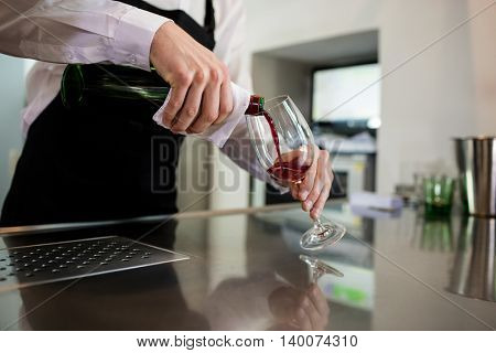 Midsection of bartender pouring wine in glass at bar counter