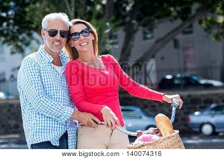 Portrait of happy mature couple riding bicycle in city