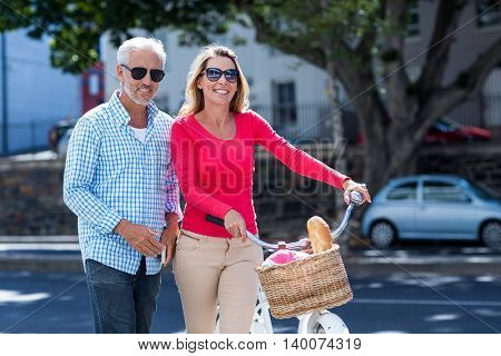 Portrait of happy mature couple with bicycle in city