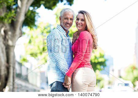 Portrait of romantic mature couple standing by tree in city