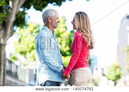 Happy romantic mature couple holding hands by tree in city