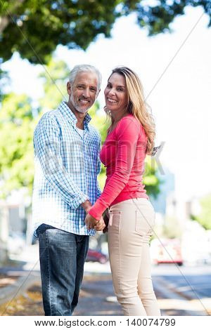 Portrait of happy mature couple holding hands by tree in city