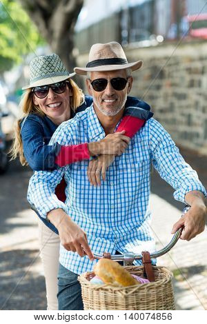 Portrait of mature couple hugging while riding bicycle in city