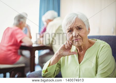 Senior woman sitting on a couch in a retirement home