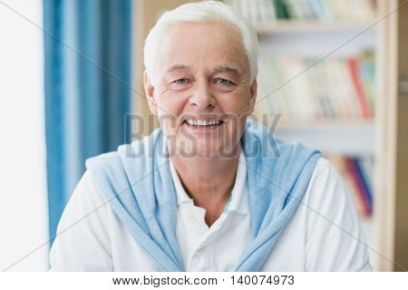 Senior man smiling at camera in a retirement home