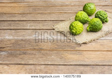 Kaffir lime on wooden table is fruits and leaves are used as a spice for thai food and etc.