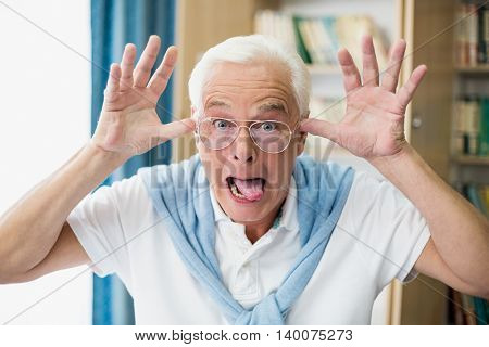 Senior man making faces in a retirement home