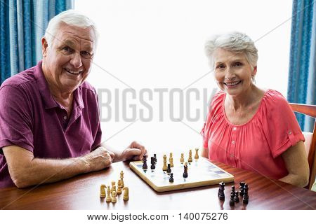 Senior couple playing chess in a retirement home