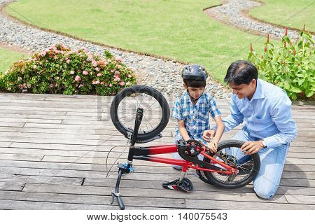 Indian man showing his son how to repair bicycle