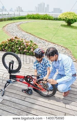 Child and father examining bicycle chain outdoors