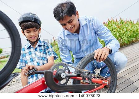 Father explaining his son work of bicycle