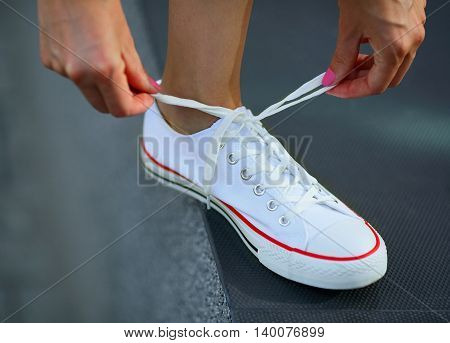 White sneaker on leg. Tying shoelace. Hipster style
