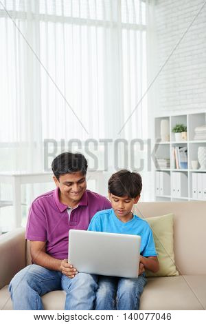 Indian father and child watching movie on laptop together
