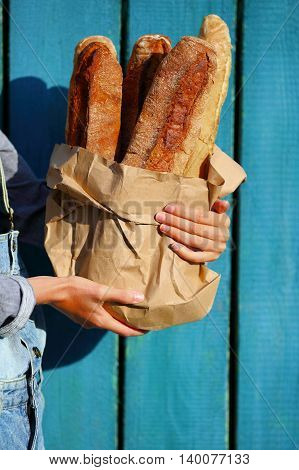 Baguettes. Paper bag with baguette in hands of woman against the wooden fence