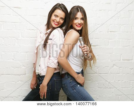 two beauty hipster girls with a microphone