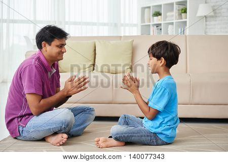 Indian father and son sitting on the floor and playing