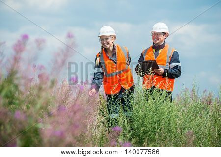 Man and woman researching recultivated field in russia