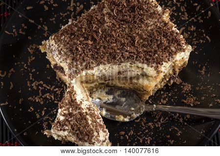 Tiramisu cake and spoon on dark plate with wooden background