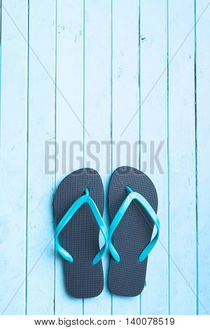 Blue flip flops on blue floor.