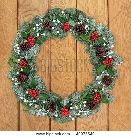 Christmas wreath with holly, mistletoe, pine cones and snow covered blue spruce fir over oak wood front door background.