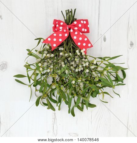 Christmas mistletoe decoration with red and white polka dot bow over distressed white wood background.