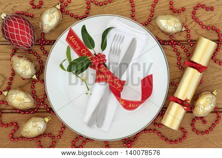 Christmas dinner table setting with white porcelain plate, red ribbon bow, napkin, cutlery, holly, mistletoe, cracker with gold and red bauble decorations over oak wood background.