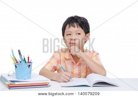 Little Asian boy thinking between doing homework