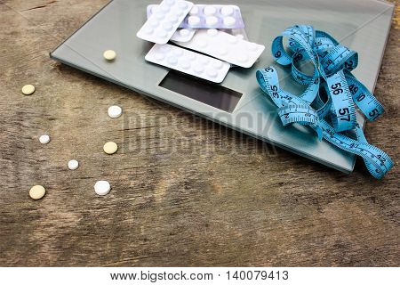 Measuring tape, pills and scales on wooden background. The concept of diet pills.