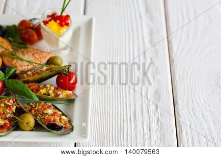 Turkish cuisine - stuffed mussels and grilled salmon on plate on white wooden background, copyspace for text. Traditional meal in Turkey restaurant
