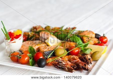 Grilled assorted seafood with sauce, blurred background with copyspace for text, focus on roasted shrimps with tomatoes and olives
