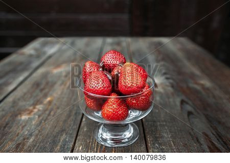 Bowl of fresh strawberries with chocolate topping on old rustic wooden table. Homemade dessert in countryside