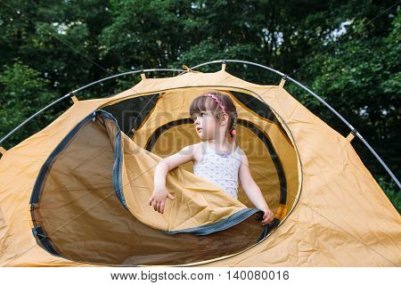Pretty little girl in tent, travel photo, wild nature background. Female child learn how to be tourist in forest.