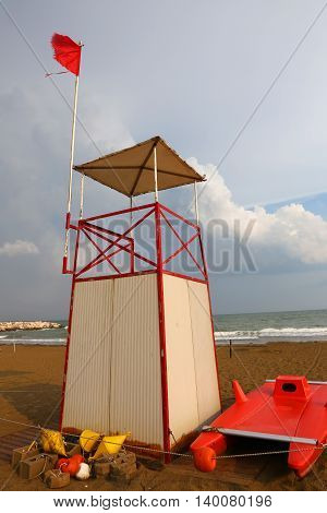 Lifeguard tower on the beach with the red flag fluttering in the wind
