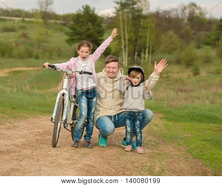father with two little daughters walking with bike in a countryside