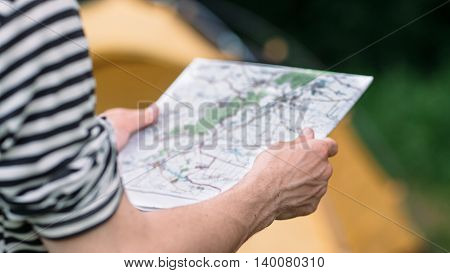 Tourist reading geographic map choosing best way. Adventure in wild nature, active lifestyle