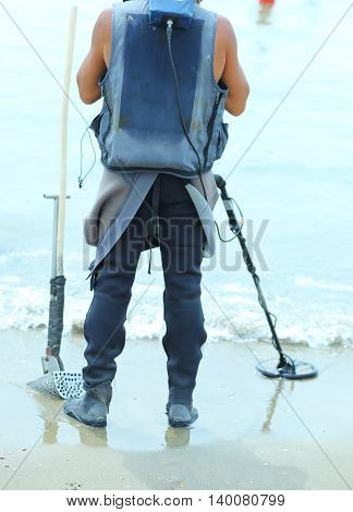 Man With Metal Detector  To Find Lost Objects Under The Sand Of