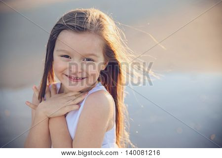 Happy little girl smiling and showing love gesture soft focus copy space background