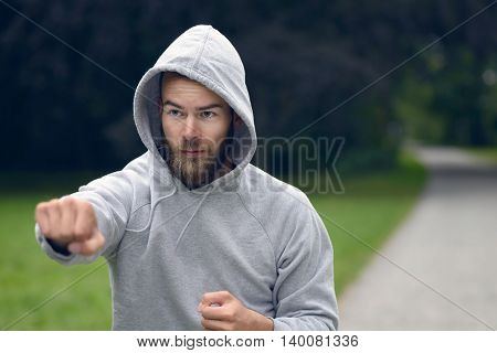 Young Man Working Out In A Park Punching Air